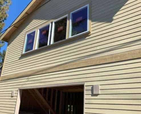New two story house construction. Siding job showing the new primed siding ready to be painted. High efficient windows instaled on 2nd floor Garage opening without door and 2x4 and 4x6 cut pieces of wood an floor, new construction, framing contractor